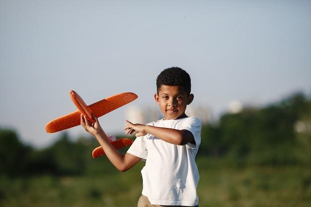 Menino africano segura o brinquedo do avião brincando sozinho. criança em um parque de verão.
