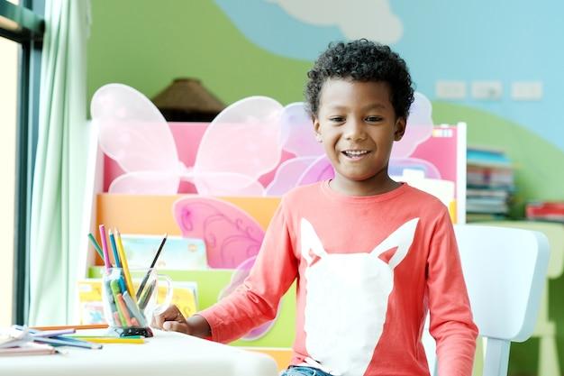 Menino africano sentado e sorrindo para sua mesa na sala de aula pré-elementar