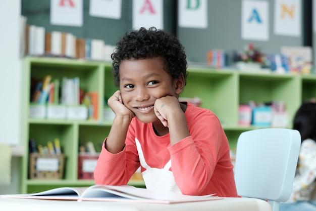 Menino africano sentado em sua mesa com rosto sorridente
