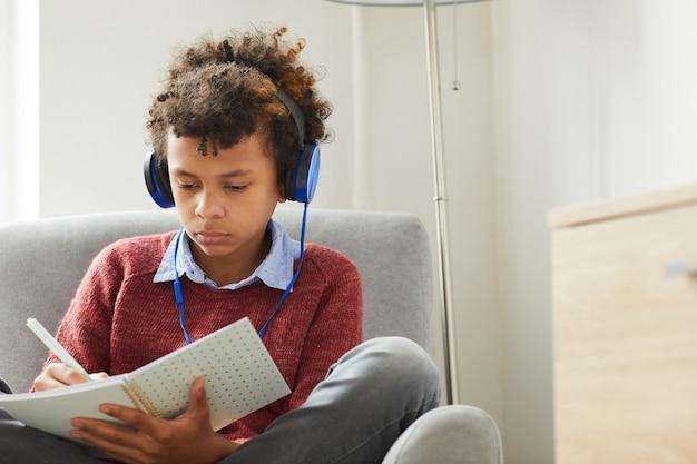 Menino africano sério usando fones de ouvido, sentado na poltrona e fazendo anotações no livro que está se preparando para as aulas em casa