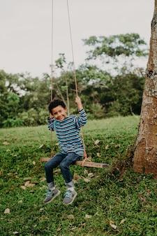 Menino afro-americano balançando em um balanço na natureza