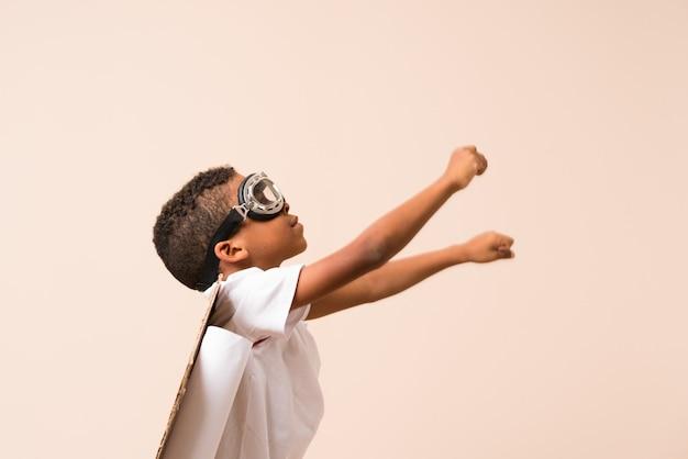 Menino afro-americano com chapéu de aviador e asas