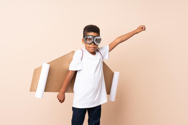 Menino afro-americano com chapéu de aviador e com asas sobre isolado
