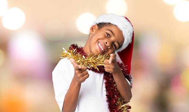 Menino afro-americano com chapéu de natal aponta o dedo para você com uma expressão confiante sobre fundo desfocado