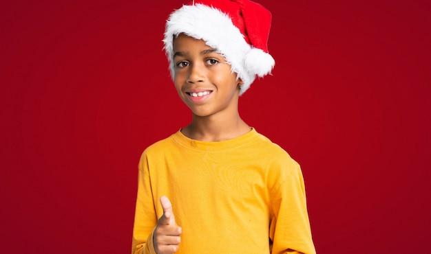 Menino afro-americano com chapéu de natal aponta o dedo para você com uma expressão confiante sobre fundo vermelho