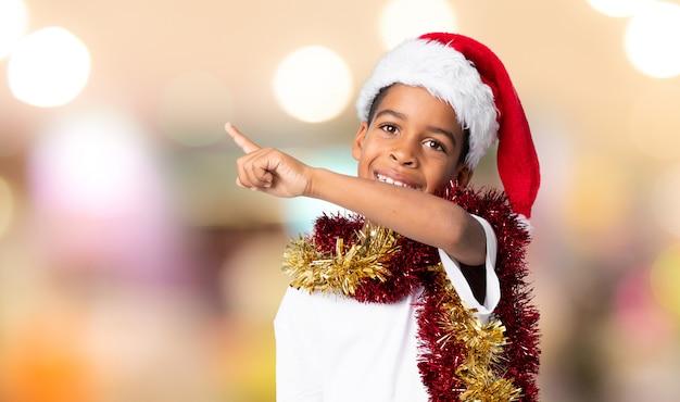 Menino afro-americano com chapéu de natal, apontando para o lado para apresentar um produto sobre fundo desfocado