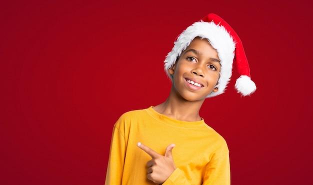Menino afro-americano com chapéu de natal, apontando para o lado para apresentar um produto sobre fundo vermelho