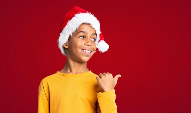 Menino afro-americano com chapéu de natal apontando para o lado para apresentar um produto sobre parede vermelha
