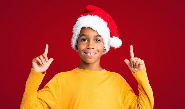 Menino afro-americano com chapéu de natal apontando uma ótima idéia sobre fundo vermelho