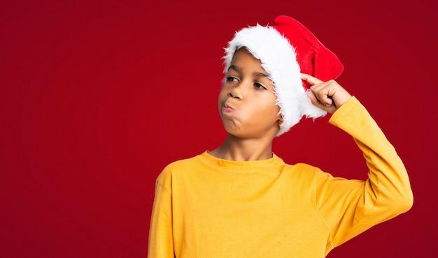 Menino afro-americano com chapéu de natal com dúvidas e com a expressão do rosto confuso sobre fundo vermelho