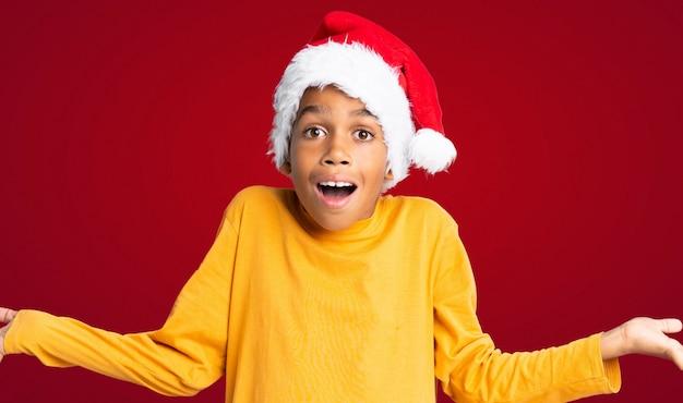 Menino afro-americano com chapéu de natal com expressão facial chocado sobre parede vermelha