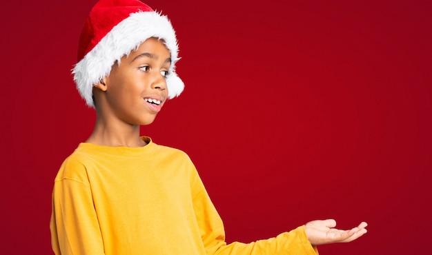 Menino afro-americano com chapéu de natal com expressão facial de surpresa sobre parede vermelha