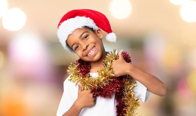 Menino afro-americano com chapéu de natal com polegares para cima, porque algo de bom aconteceu sobre o fundo desfocado