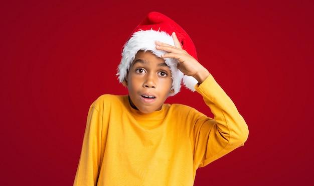 Menino afro-americano com chapéu de natal com surpresa e expressão facial chocada sobre fundo vermelho