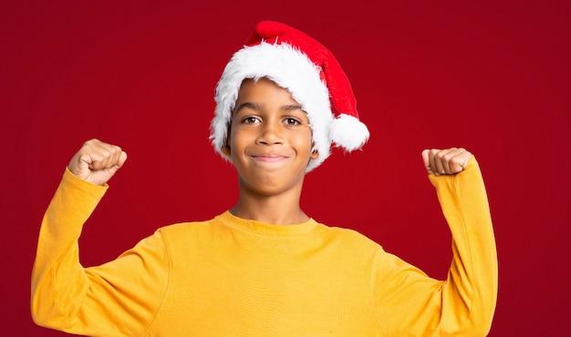Menino afro-americano com chapéu de natal comemorando uma vitória sobre fundo vermelho