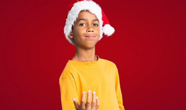 Menino afro-americano com chapéu de natal, convidando para vir com a mão. feliz que você veio sobre o fundo vermelho