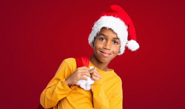 Menino afro-americano com chapéu de natal e levar uma sacola com presentes ao longo da parede vermelha