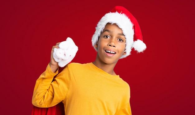 Menino afro-americano com chapéu de natal e levar uma sacola com presentes e fazendo o gesto de surpresa sobre fundo vermelho