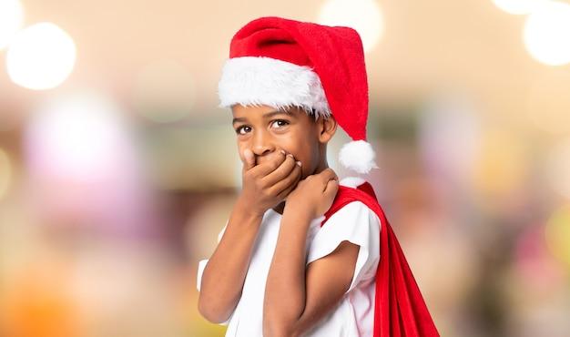 Menino afro-americano com chapéu de natal e levar uma sacola com presentes, fazendo o gesto de surpresa sobre fundo desfocado