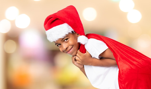Menino afro-americano com chapéu de natal e levar uma sacola com presentes sobre fundo desfocado