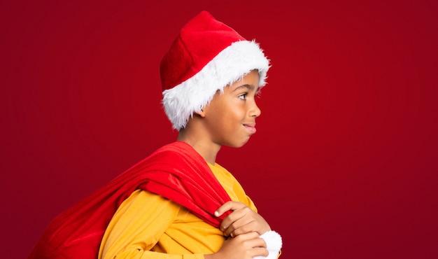 Menino afro-americano com chapéu de natal e levar uma sacola com presentes sobre fundo vermelho