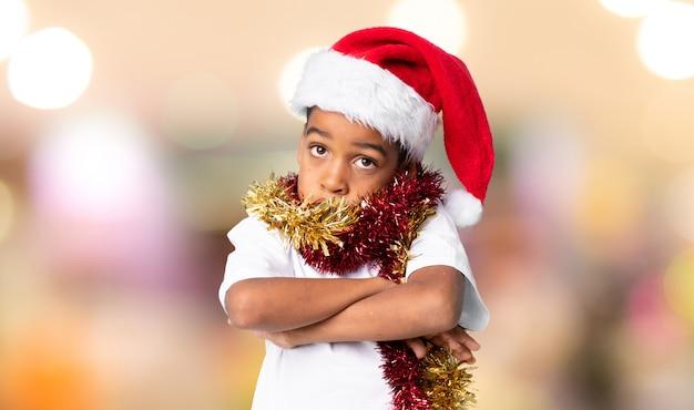 Menino afro-americano com chapéu de natal, fazendo dúvidas gesto enquanto levanta os ombros sobre fundo desfocado
