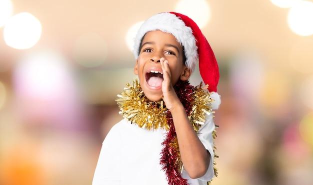 Menino afro-americano com chapéu de natal, gritando com a boca aberta sobre fundo desfocado