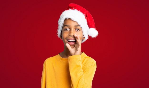 Menino afro-americano com chapéu de natal gritando com a boca aberta sobre parede vermelha