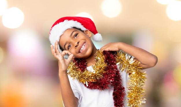 Menino afro-americano com chapéu de natal, mostrando sinal de ok com os dedos sobre fundo desfocado