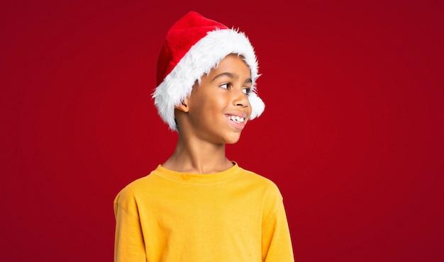 Menino afro-americano com chapéu de natal, olhando de lado por cima da parede vermelha