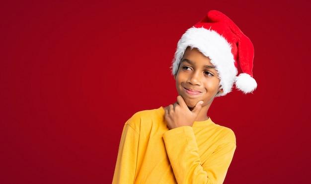 Menino afro-americano com chapéu de natal, olhando de lado sobre fundo vermelho