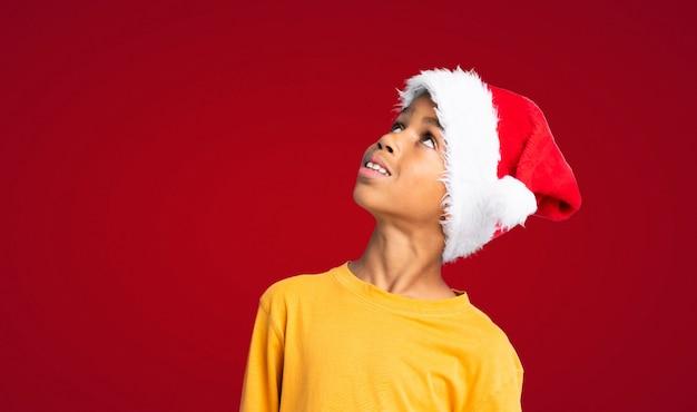 Menino afro-americano com chapéu de natal, olhando para cima enquanto sorrindo sobre parede vermelha