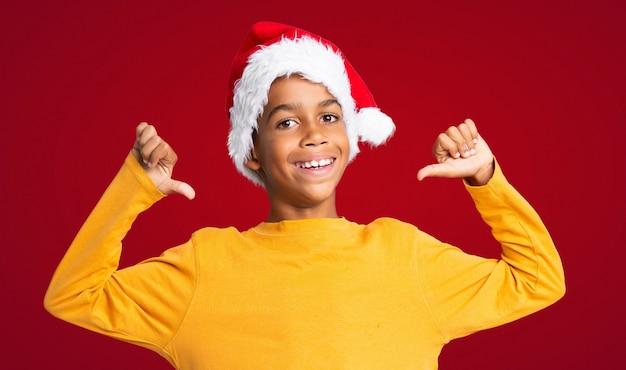 Menino afro-americano com chapéu de natal orgulhoso e auto-satisfeito sobre parede vermelha