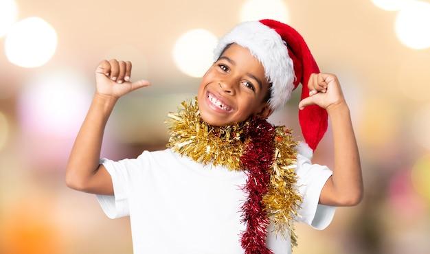 Menino afro-americano com chapéu de natal orgulhoso e satisfeito sobre fundo desfocado