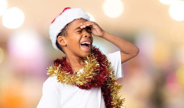 Menino afro-americano com chapéu de natal percebeu algo e pretendendo a solução sobre parede desfocada