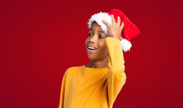 Menino afro-americano com chapéu de natal percebeu algo e pretendendo a solução sobre parede vermelha