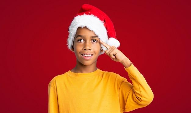 Menino afro-americano com chapéu de natal, pretendendo realizar a solução sobre fundo vermelho