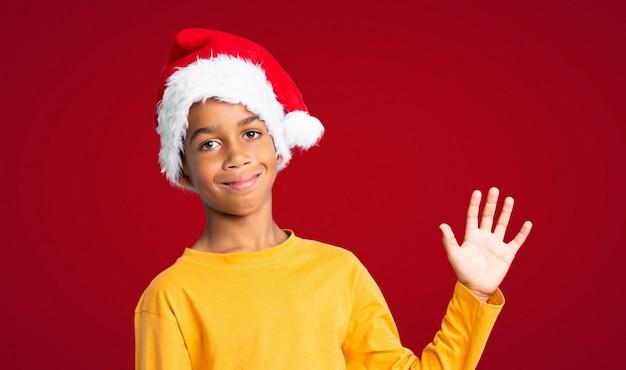 Menino afro-americano com chapéu de natal saudando com a mão com expressão feliz sobre fundo vermelho
