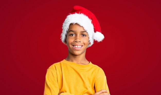 Menino afro-americano com chapéu de natal sobre fundo vermelho