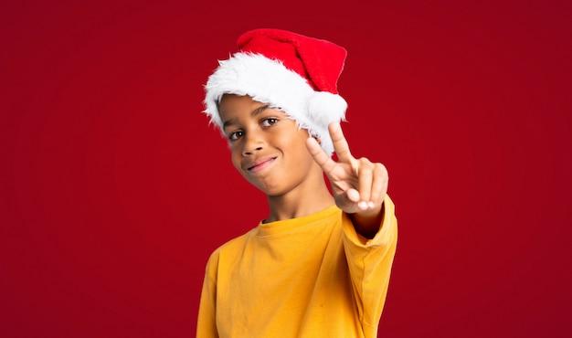 Menino afro-americano com chapéu de natal sorrindo e mostrando sinal de vitória sobre fundo vermelho