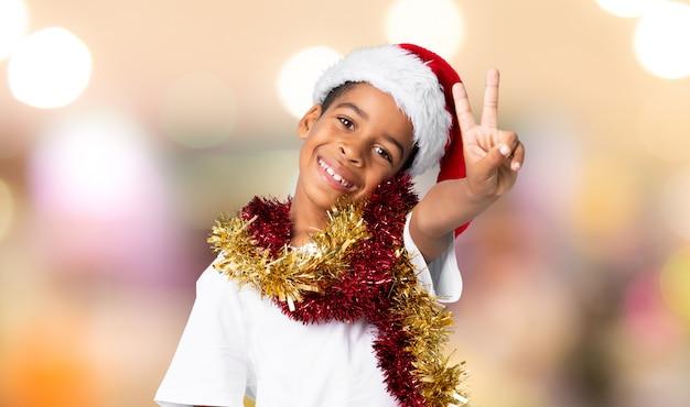 Menino afro-americano com chapéu de natal sorrindo e mostrando sinal de vitória sobre parede desfocada