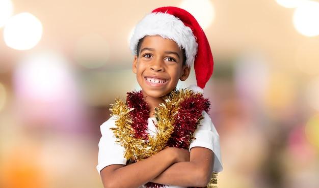 Menino afro-americano com chapéu de natal sorrindo muito sobre fundo desfocado