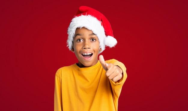 Menino afro-americano com chapéu de natal surpreso e apontando a frente sobre fundo vermelho