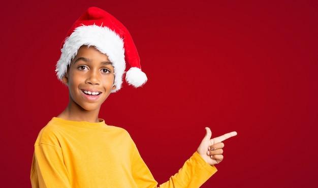Menino afro-americano com chapéu de natal surpreso e apontando o lado ao longo da parede vermelha