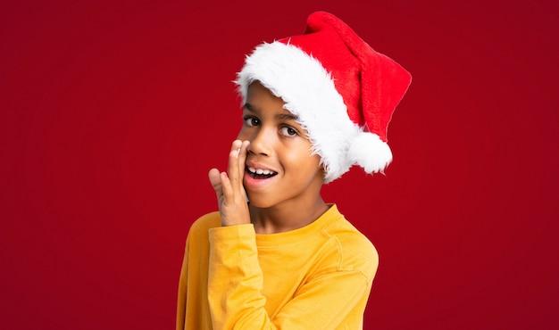 Menino afro-americano com chapéu de natal sussurrando algo sobre fundo vermelho
