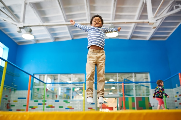 Menino afro-americano, desfrutando de trampolins