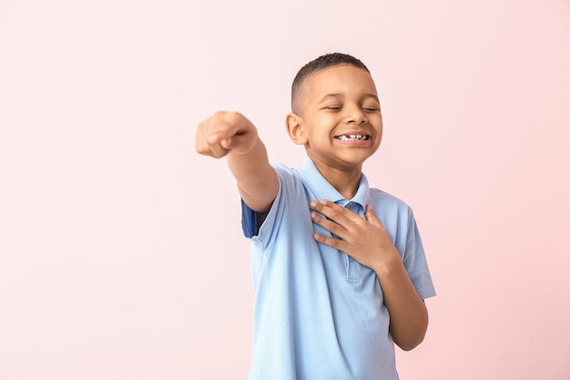 Menino afro-americano feliz apontando para o visor contra a cor