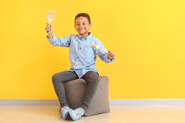 Menino afro-americano fofo com pincéis perto da parede colorida