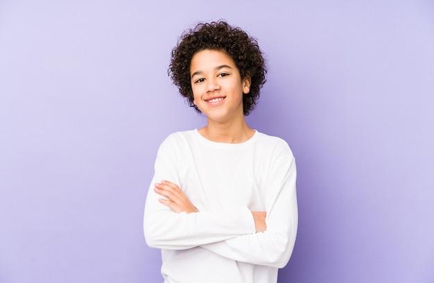 Menino afro-americano isolado que se sente confiante, cruzando os braços com determinação.