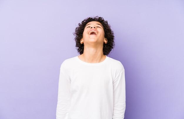 Menino afro-americano isolado relaxado e feliz rindo, pescoço esticado, mostrando os dentes.